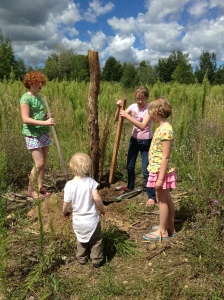 The Tengelitsch-Graves kids plant fence posts for the future sheep pasture last summer.
