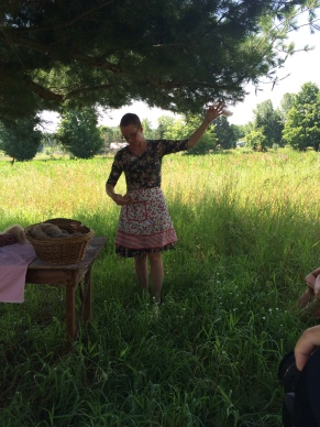 Drop spindle demonstration. (Note: Cherry apron in celebration of the season). Photo by the lovely Holly Pharmer